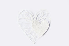 Two white paper lace hearts on light background Royalty Free Stock Image