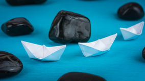 Two White Paper Ships in Sigle File between Abstract Black Rock Stones on Blue Background Stock Photos
