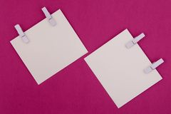 Two white papers with clothespins on a purple background. Copy space. royalty free stock images