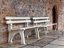 White Park Benches Beside Stone Wall. Two white park benches in a flagstone courtyard beside a stone church wall, Macedonia, Northern Greece Royalty Free Stock Photos