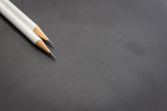Two white pencils on black Royalty Free Stock Photos