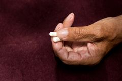 Two white pills in old men`s hands . Painful old age. Health care of older people.  Royalty Free Stock Photo