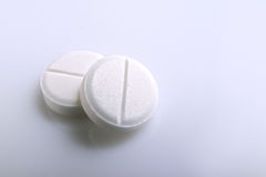 Two white pills on a table. Two round white pills on a glass table Stock Photo