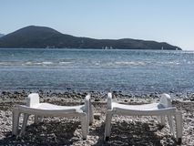 Two white plastic chaise lounge on sea side. Two empty white plastic chaise lounge laid out on sea side pebbles, mountains and yacht on background stock image