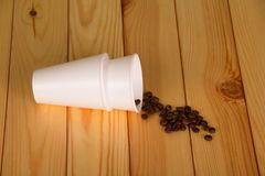Two white plastic Cup lying on table, next to scattered coffee beans. Two white plastic Cup lying on wooden table, next to scattered coffee beans Royalty Free Stock Photography