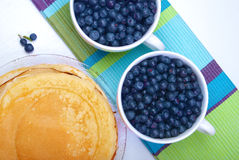 Two white plates with blueberries and pancakes. On white table Royalty Free Stock Photo