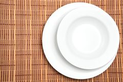Two White Plates with Copy Space. Two white plates or dishes photographed over a wooden placement background with copy space on the left. Suitable for restaurant royalty free stock images