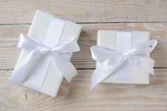 Two White Presents. High angle image of two presents wrapped in white paper and ribbons. Horizontal format on a whitewashed rustic wood table Royalty Free Stock Photos