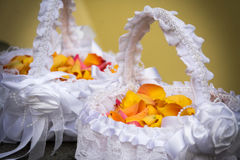 Wedding decoration. Two white punnets filled with colorful petals as a wedding decoration with a yellow background Stock Images