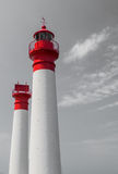 Two white and red lighthouses on grey sky Royalty Free Stock Photo