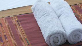 Two white rolled towels on a bed. / two white towels stock footage