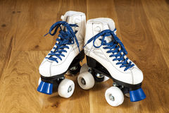 Two white roller skates. Pair of roller skates on a wooden background Royalty Free Stock Photo