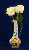 Two white roses in a decorated vase. With blue background Royalty Free Stock Photo
