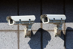 Two white security cameras on the concrete wall Stock Images