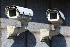 Two white security CCTV cameras  on the wall. White security CCTV cameras  on the wall Royalty Free Stock Photography
