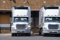 Semi tractor trailer trucks at a loading dock Stock Photos