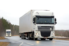 Two White Semi Trucks on Rural Road. SALO, FINLAND - JANUARY 30, 2016: Two white cargo trucks transport goods along rural road. The import at the Port of Royalty Free Stock Images