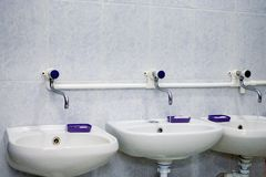 Two white sinks and liquid soap in public toilet. stock images