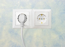 Two white socket outlet with one connected corresponding power p. Block of the two white socket outlets European standard with connected one white power cable stock photo
