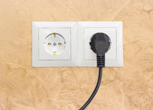 Two white socket outlets with one connected corresponding power. Block of the two white socket outlets European standard with connected one black power cable stock photography