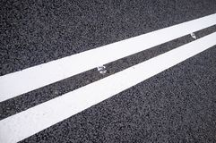 Two white solid lines on a new asphalt road. royalty free stock photos