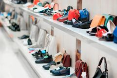 Two white store shelves with multi-colored bags and shoes stock photo