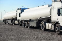 Two white tank trucks on the road, clear and blank space on the Royalty Free Stock Image