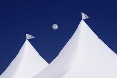 Two white tents with white flags, full moon and deep blue sky Royalty Free Stock Photo