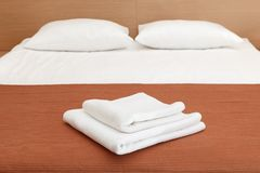 Two white Terry towels on the bed in the hotel room stock photography