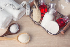 Two white towels, basket with hampoo, cream, lotion bottles, wis. P of bast, measuring tape, sand and sea salt on wood. Bath, sauna, Spa slimming, weight loss Stock Photo