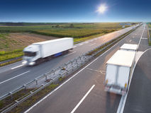 Two white trucks on highway at sunny day Stock Photo