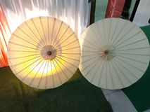 Two white umbrellas on the floor. stock image