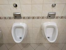 Two White urinal, pissoir on wall. Two White urinal, pissoir on a wall, clean, no eople stock photography