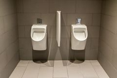 Two white urinals in the men`s room in a modern office building. stock photo