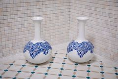 Two white vases with blue patterns standing on a beige broom with blue lines on the background of a wall of beige marble tiles in stock images
