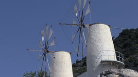 Two white windmills turning slowly. Low angle front side view of two old traditional white windmills turning slowly stock video
