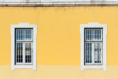 Two white windows on a yellow wall. In portugal Stock Images