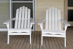 Two white wooden adirondack chair on old weathered front porch. At white bungalow Stock Image