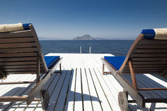 Two white wooden beach couches on a plank pier near the blue sea. Against the backdrop of mountains in the distance Stock Photos