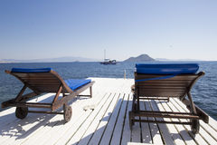 Two white wooden chaise longues on a wooden pier by the sea agai Stock Images