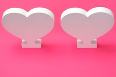Two White Wooden Heart On The Pink Paper Background Stock Images