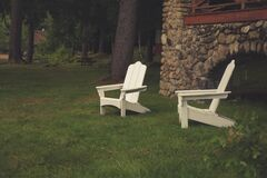 Two White Wooden Lawn Chairs in Grass by Home Royalty Free Stock Images