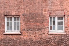 Two white wooden sash windows on a restored red brick wall of a. Victorian house residential building Royalty Free Stock Photo