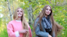 Two white young stylish girl with long hair dancing in the autumn on the nature. Two trendy stylish young woman having fun dancing in the park autumn day stock footage
