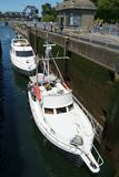 Two whitepleasure boats entering locks. SEATTLE, WASHINGTON, USA JULY 7, 2017: Two white pleasure boats enter the small lock at Hiram Chittenden Locks Ballard Stock Photo
