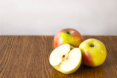 Two whole apple and half lying on a wooden table Royalty Free Stock Photography