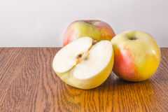 Two whole apple and half lying on a wooden table Stock Photography