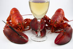 Two Lobsters Wine Glass. Two whole cooked lobsters holding a seafood fork and glass of white wine royalty free stock image