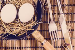 Two whole eggs in a cast iron frying pan on a wooden table. Cooking eggs stock images