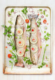 Two whole fish with ingredients on baking pan stock images